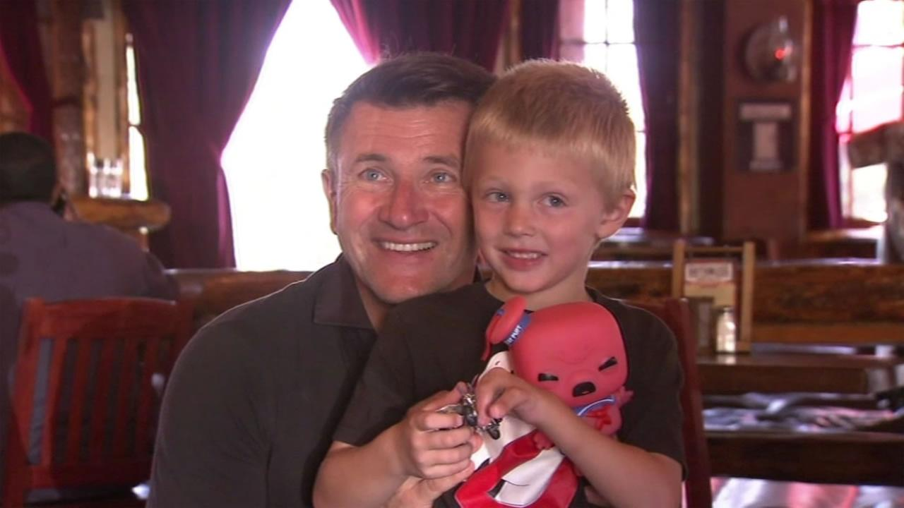 The star of the ABC show Shark Tank, Robert Herjavec, poses with Liam Brenes during a party in his honor.