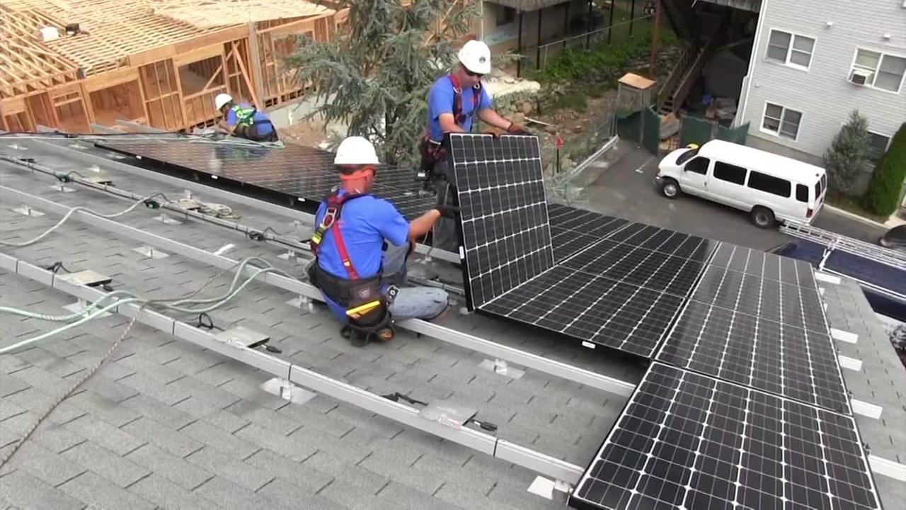 Men are seen installing solar panels on a home in this undated image.