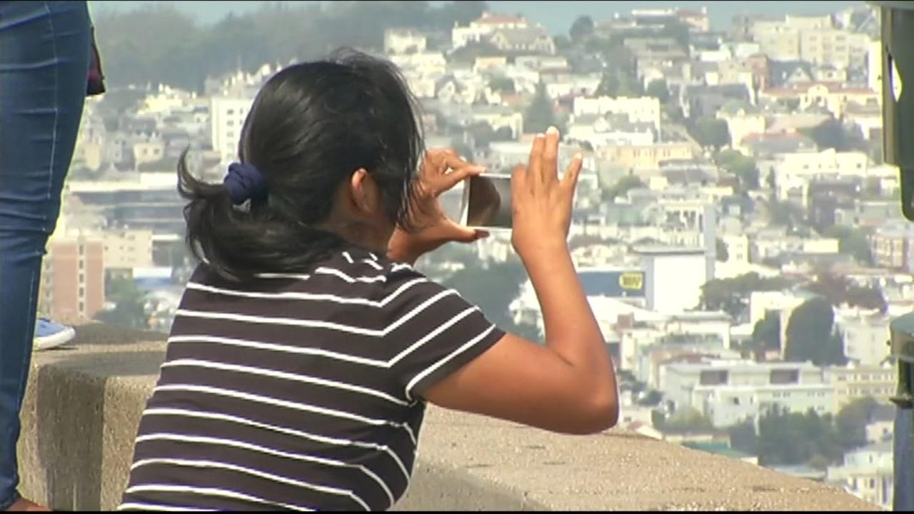 This image shows tourists at Twin Peaks in San Francisco snapping photos.