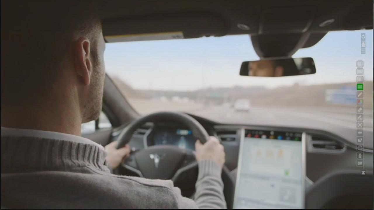 This image shows someone testing one of Teslas self-driving cars.