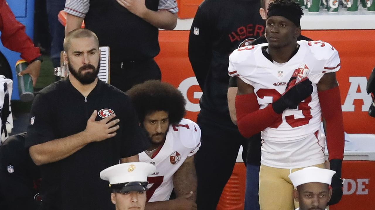 San Francisco 49ers quarterback Colin Kaepernick, middle, sits during the national anthem before an NFL preseason football game against the San Diego Chargers, Sept. 1, 2016.
