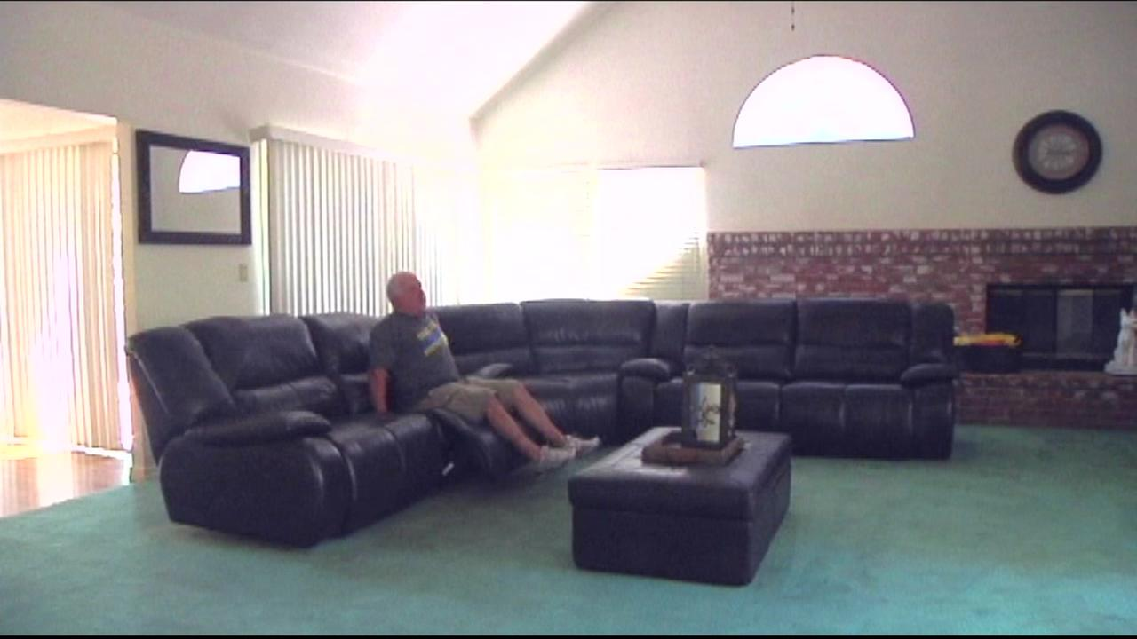 This image shows Mark McDonough on his couch at his East Bay home.