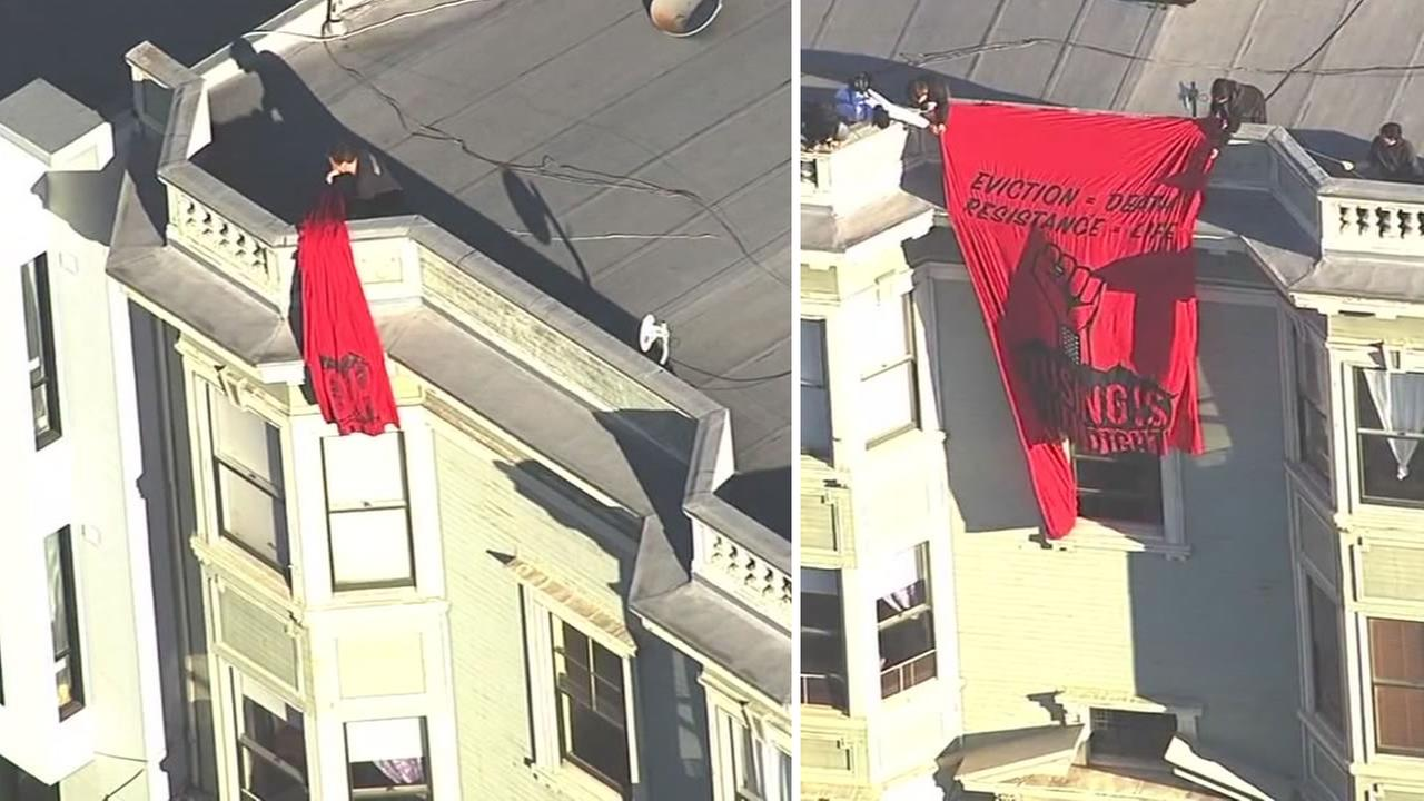 This image shows a fed up tenant removing a protest banner from an apartment building in San Francisco. Protesters were fighting the eviction of an elderly woman from her home.