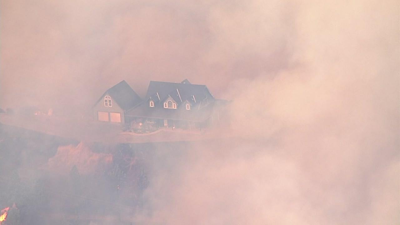 A home is surrounded by smoke from the Loma Fire burning in the Santa Cruz Mountains on Monday, September 26, 2016.