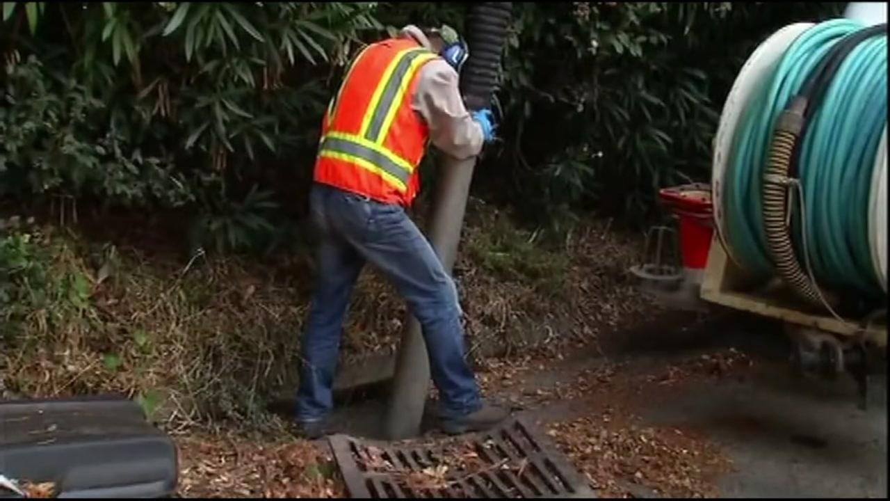 A PG&E employee works to clear a storm drain in Novato, Calif. on Thursday, October 13, 2016.