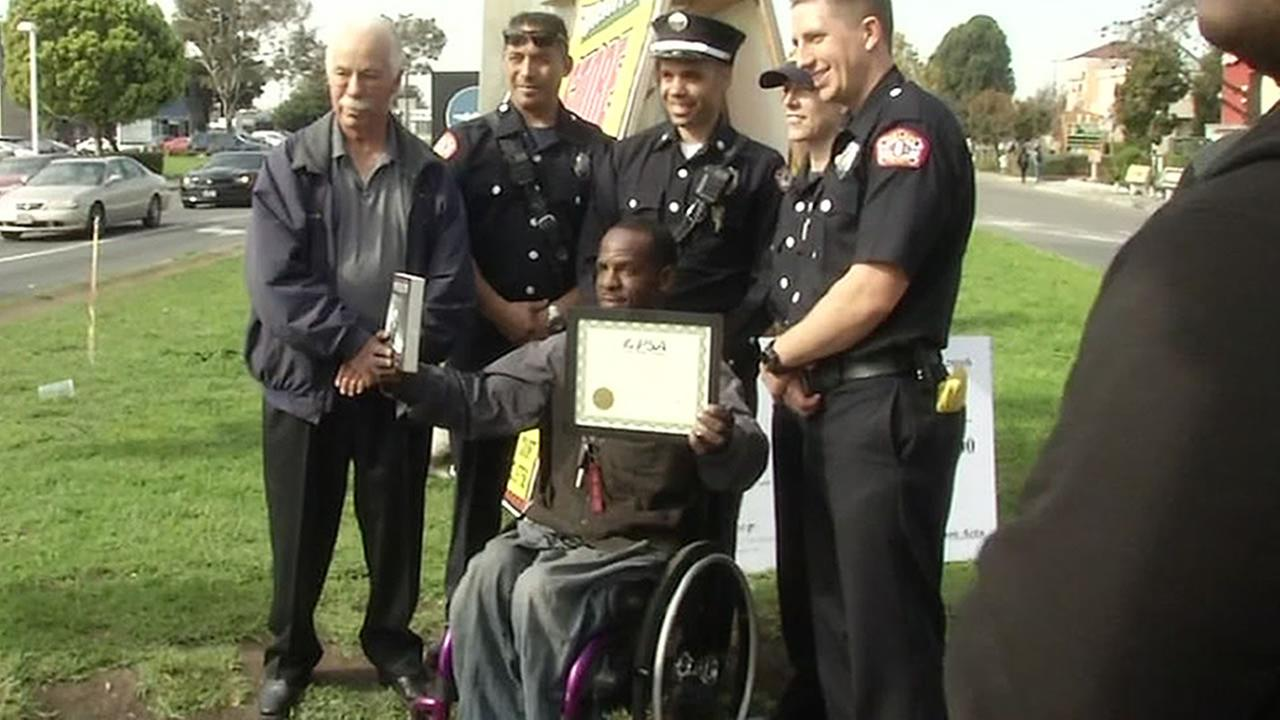 Officials are seen presenting a $10,000 check to a man paralyzed in a shooting in Oakland, Calif. on November 7, 2016 to help him become a flight instructor.