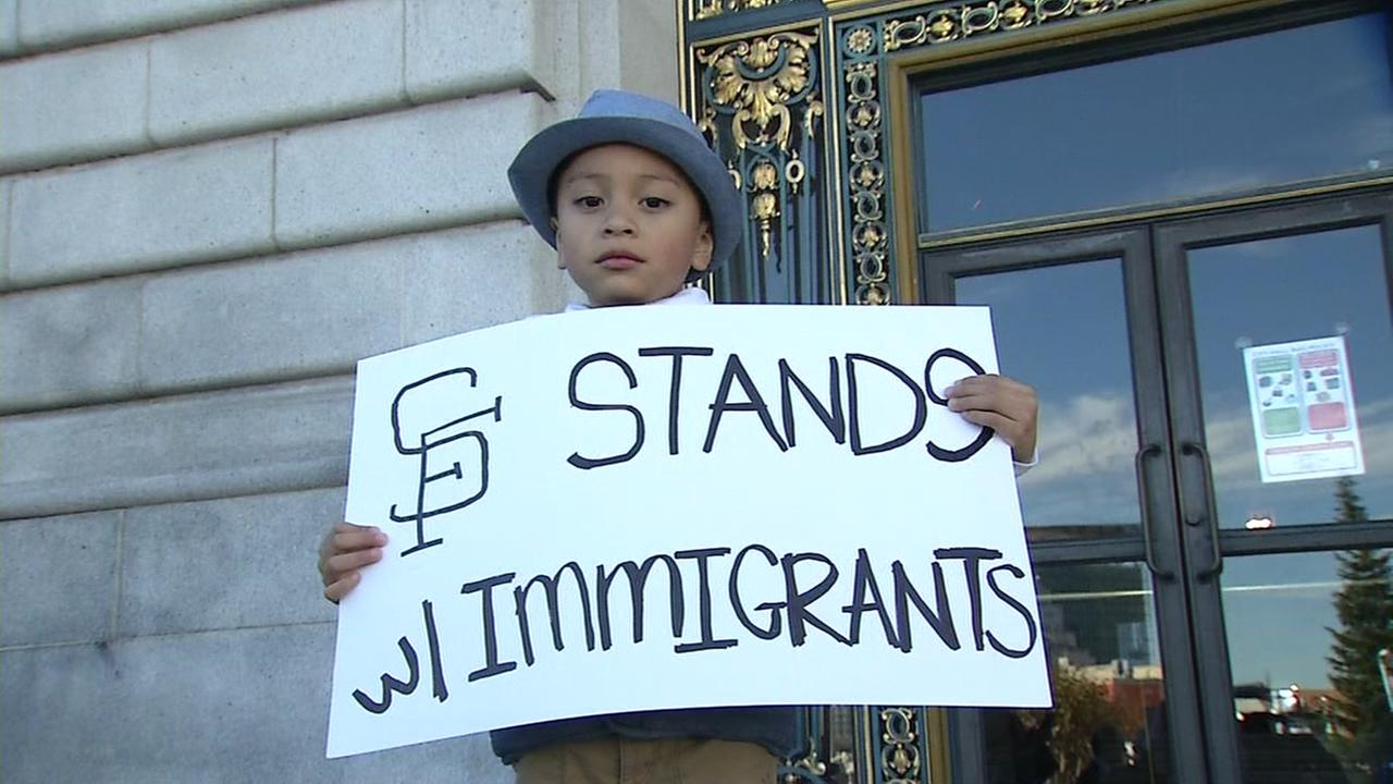 A young boy holds up a sign that reads: SF stands w/ immigrants in front of San Francisco City Hall on Tuesday, November 29, 2016.