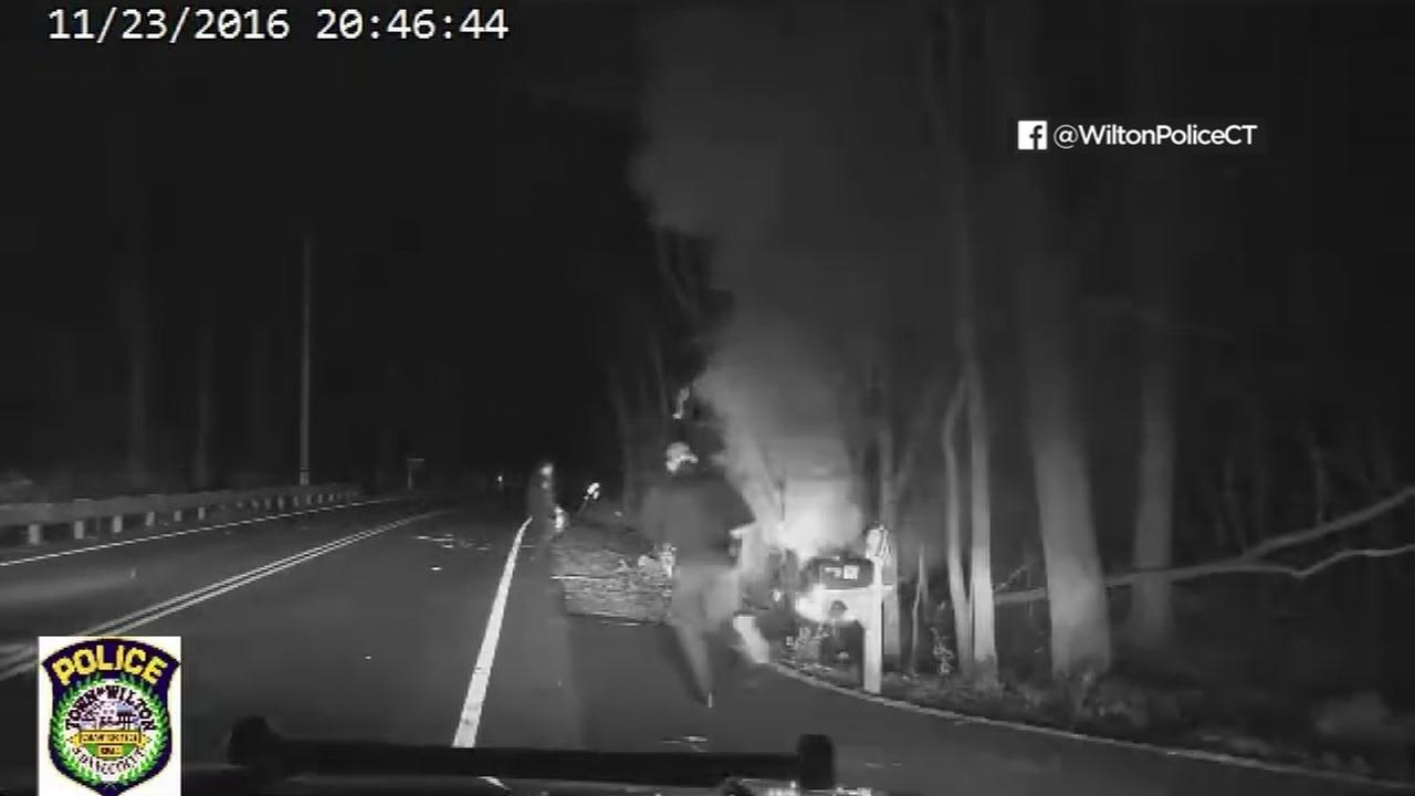 Dashcam video captures police officers in Connecticut helping a person trapped inside a burning car.
