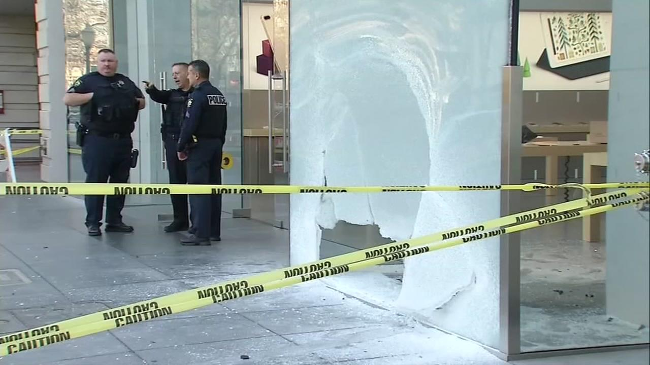 An Apple store with its window smashed in is seen in Palo Alto, Calif.