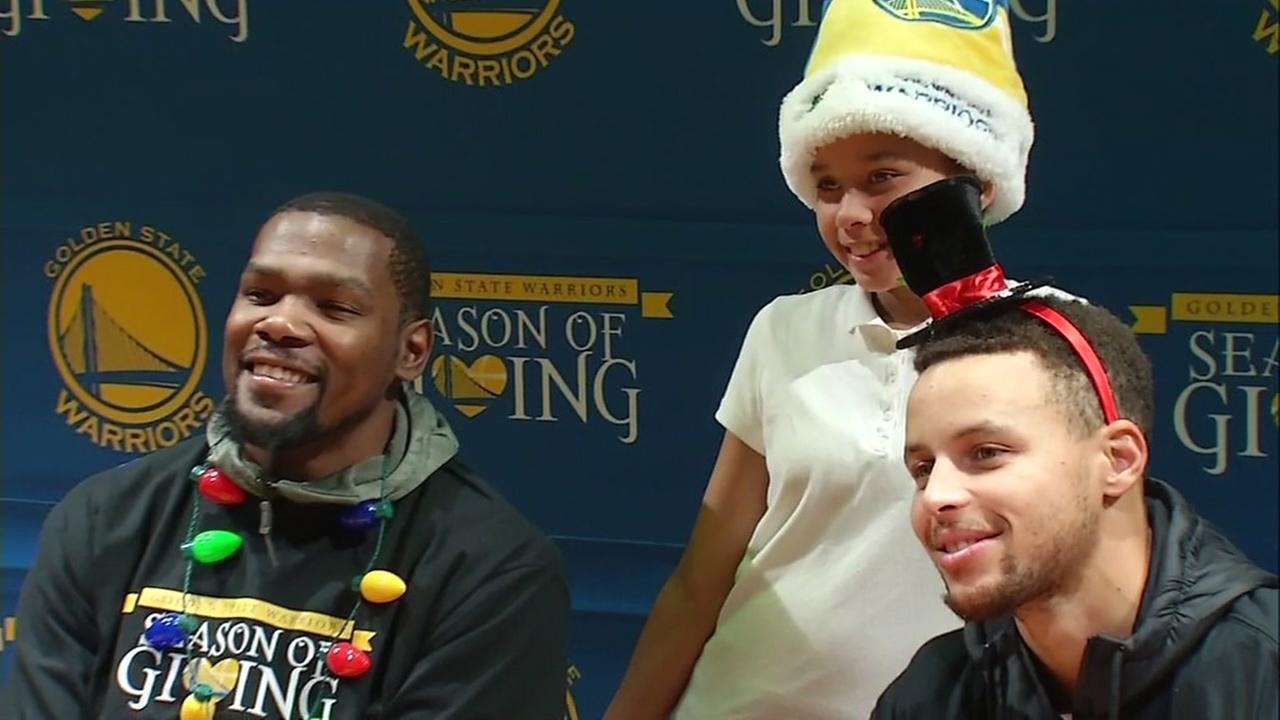 Golden State Warriors players are seen posing for a photo with a young girl at a school in San Franciscos Bayview District on Friday, December 16, 2016.