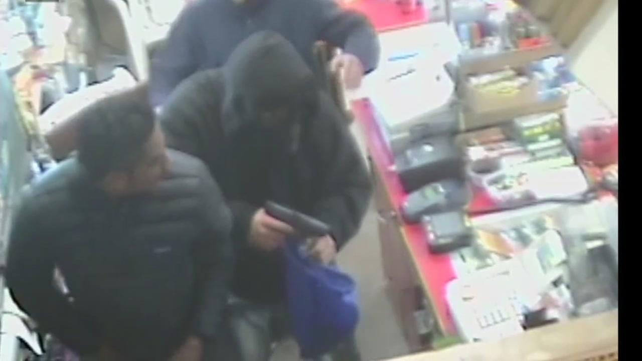 An armed robbery suspect holding a gun is seen with two clerks from the Royal Market convenience store in Hayward, Calif. on Friday, December 23, 2016.