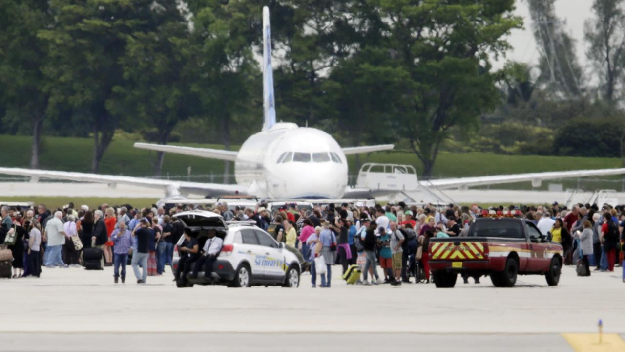 People stand on the tarmac at the Fort Lauderdale-Hollywood International Airport after a shooter opened fire inside a terminal on Jan. 6, 2017, in Fort Lauderdale, Fla. (AP Photo)
