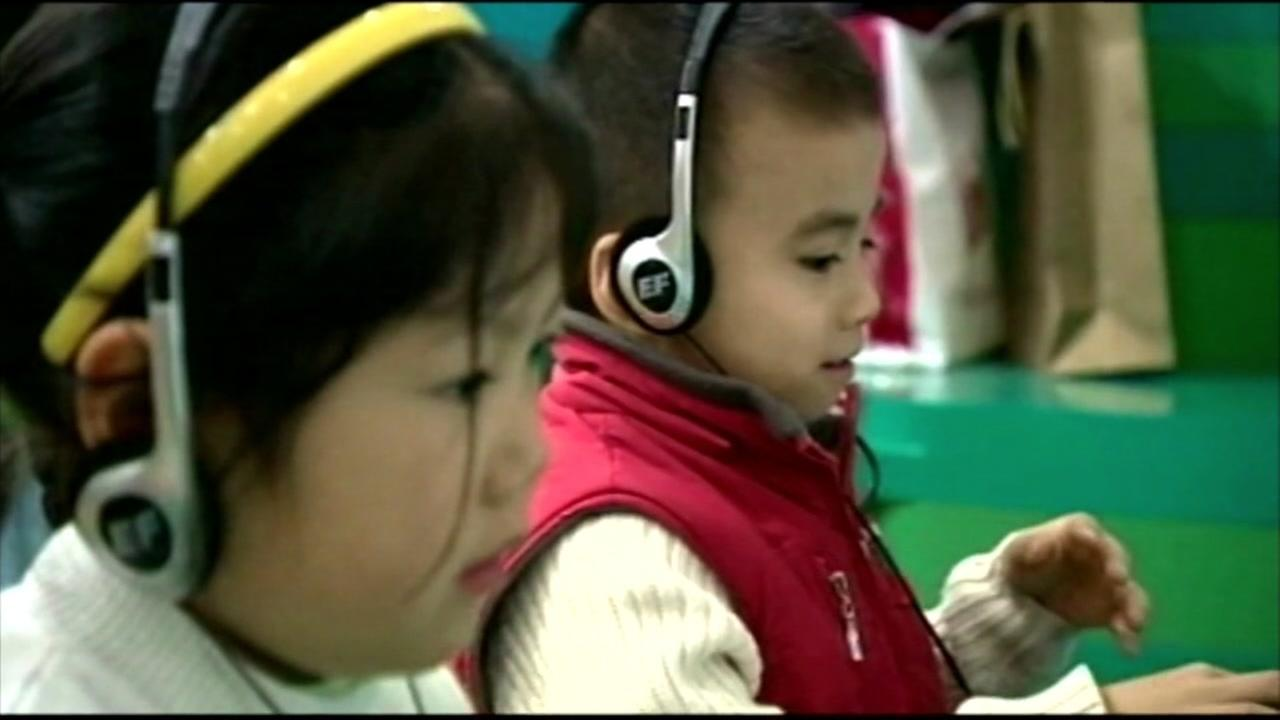 Two kids are seen listening to their headphones as they sit in front of a computer in this undated image.