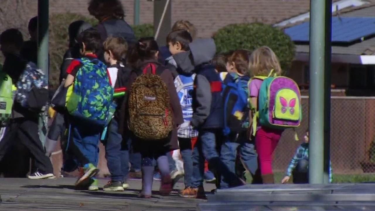 Young students wearing backpacks are seen walking through a school in the East Bay in this undated image.