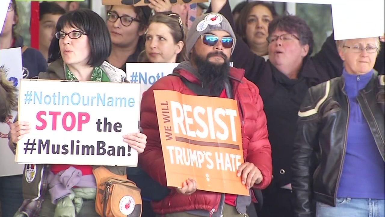 Anti-Trump protesters hold signs at the San Francisco International Airport on Saturday, January 28, 2017.