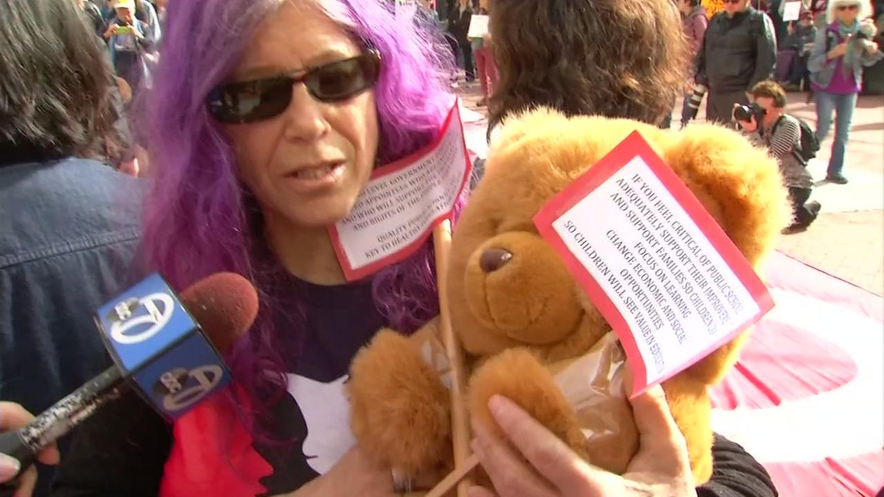 A woman holds a teddy bear in Oakland, California during a protest of Secretary of Education nominee Betsy DeVos.