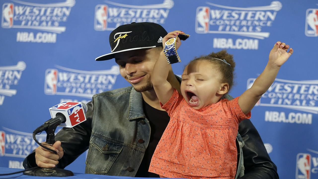 Golden State Warriors guard Stephen Curry is joined by his daughter Riley at a news conference after Game 5 of the NBA basketball Western Conference Finals May 27, 2015.