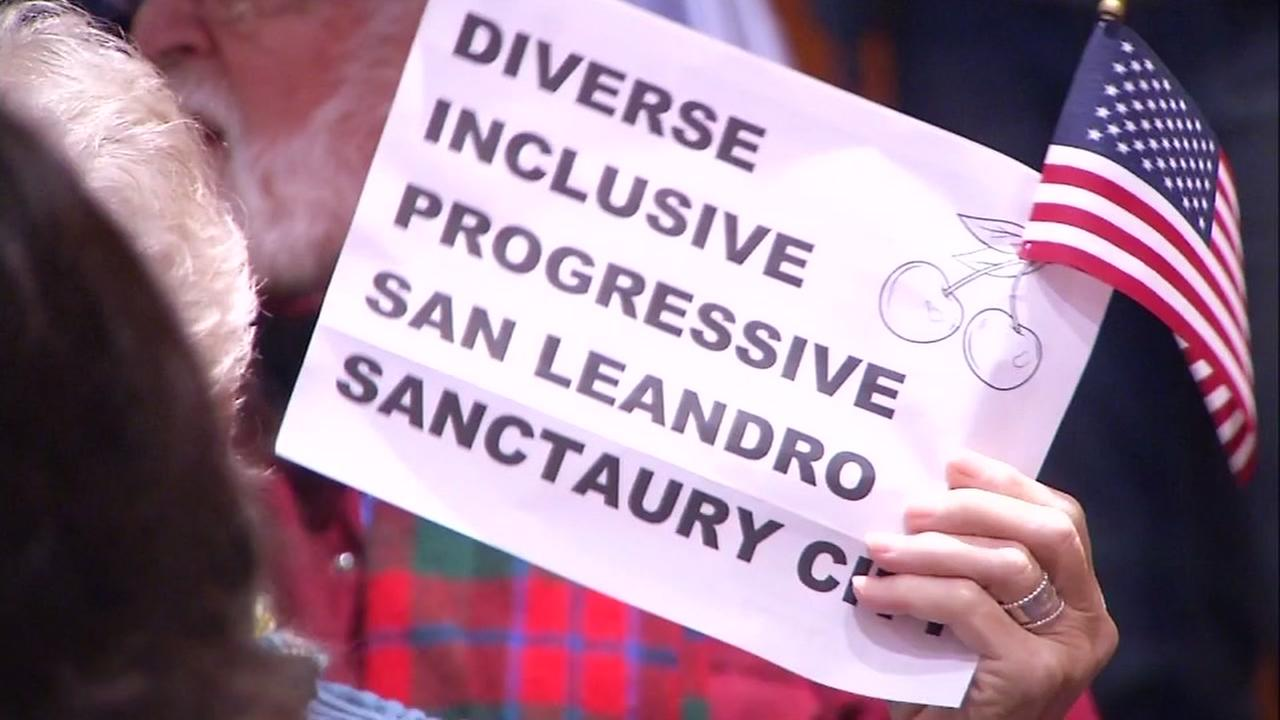 Someone holds up a sign at a San Leandro City Council meeting in San Leandro, Calif. on Feb. 21, 2017.