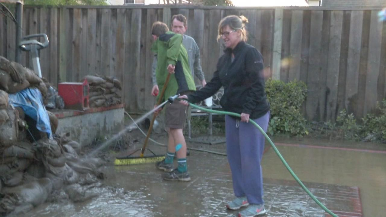 Residents are seen cleaning up in the backyard of a San Jose, Calif. home on Thursday February 23, 2017.