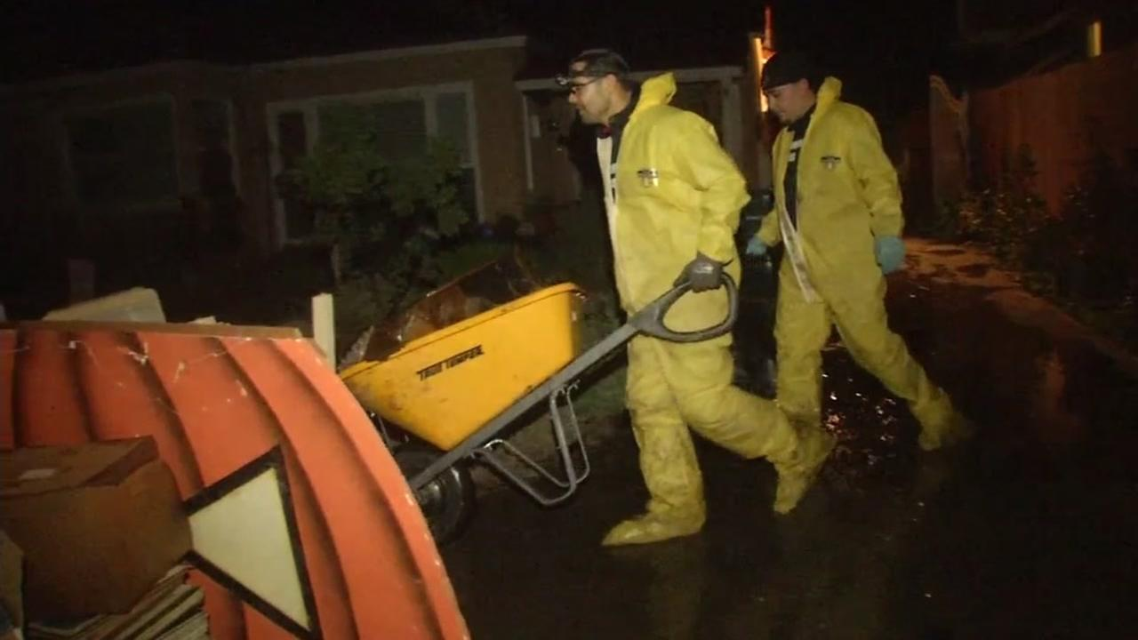 Two men in hazmat suits wheel debris away from a San Jose, Calif. home on Feb. 23, 2017.