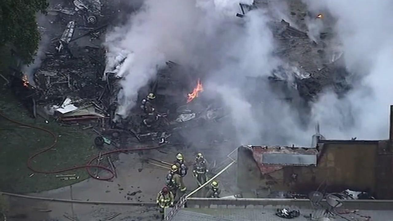 Firefighters wade through the wreckage of a plane crash in Riverside, Calif. on Feb. 27, 2017.