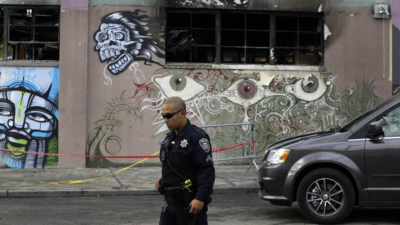 An Oakland police officer guards the area in front of the Ghost Ship warehouse in the aftermath of a fire on Friday, Dec. 9, 2016, in Oakland, Calif. (AP Photo/Ben Margot)