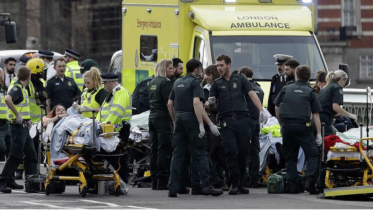 Emergency services staff provide medical attention close to the Houses of Parliament in London, Wednesday, March 22, 2017.(AP Photo/Matt Dunham)