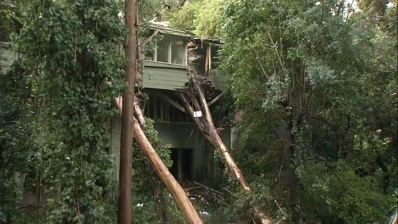 A tree falls into a home in Oakland, Calif. on Friday, April 7, 2017.