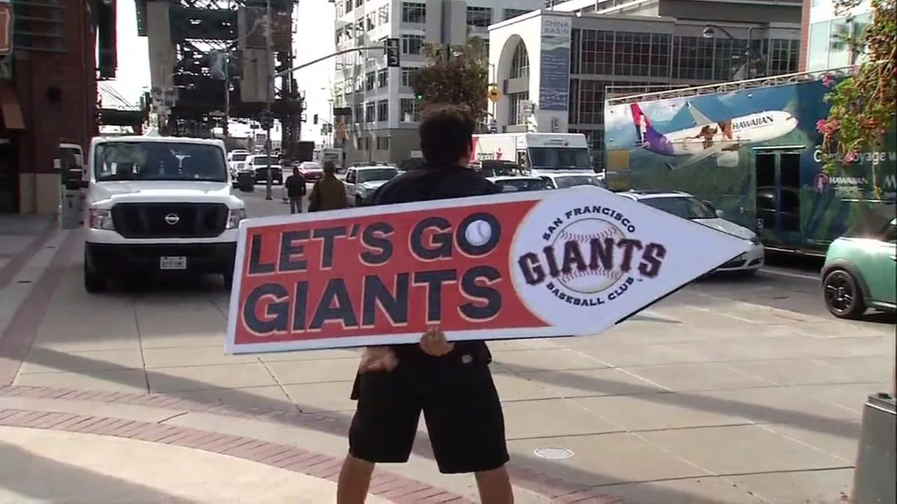 A San Francisco Giants fan holds up a sign outside AT&T Park in San Francisco, Calif. on Monday, April 10, 2017.