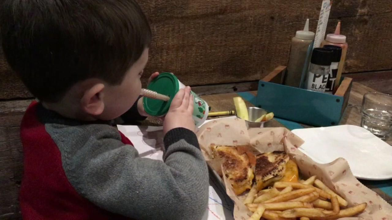 This is an undated image of a child eating a cheeseburger and french fries.
