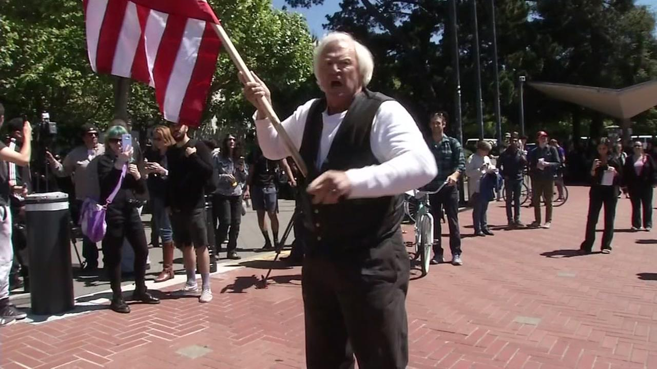 A demonstrator holds an American flag during a protest in Berkeley, Calif. on Thursday, April 27, 2017.