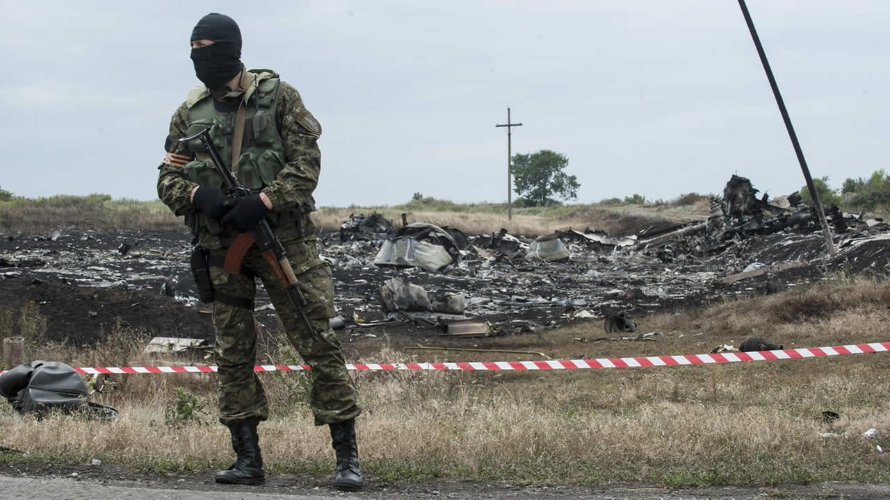 A pro-Russian fighter guards the crash site of a Malaysia Airlines jet near the village of Hrabove, eastern Ukraine, Saturday, July 19, 2014.(AP Photo/Evgeniy Maloletka)