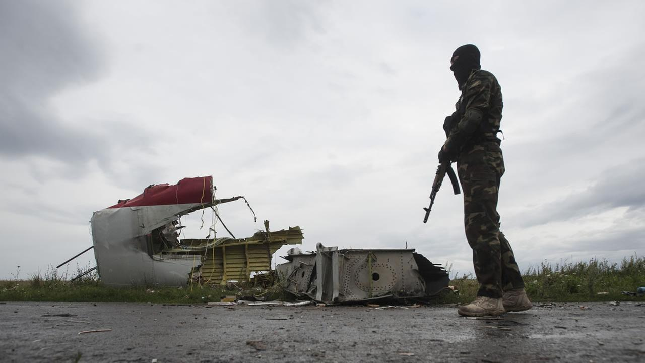 A pro-Russia fighter secures the area on the arrival of the OSCE delegation at the crash site of a Malaysia Airlines passenger jet. (AP Photo/Evgeniy Maloletka)