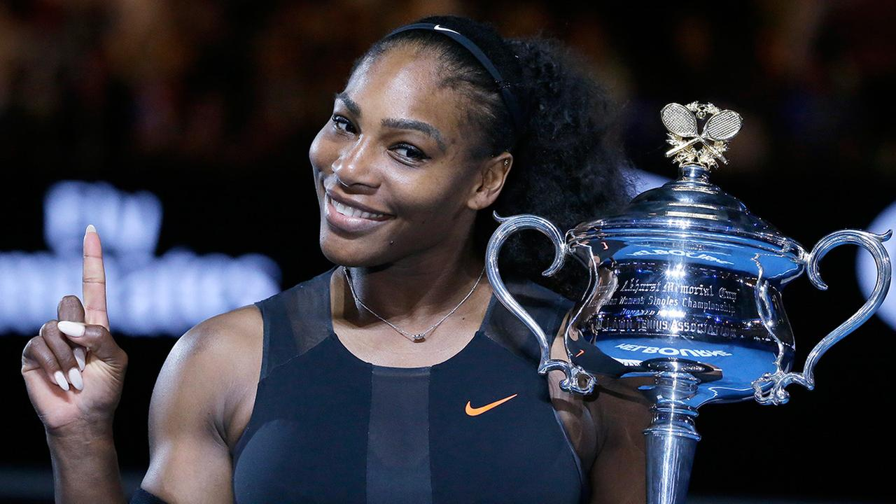 In this Jan. 28, 2017, file photo, Serena Williams holds up a finger and her trophy after winning the womens final at the Australian Open tennis championship.