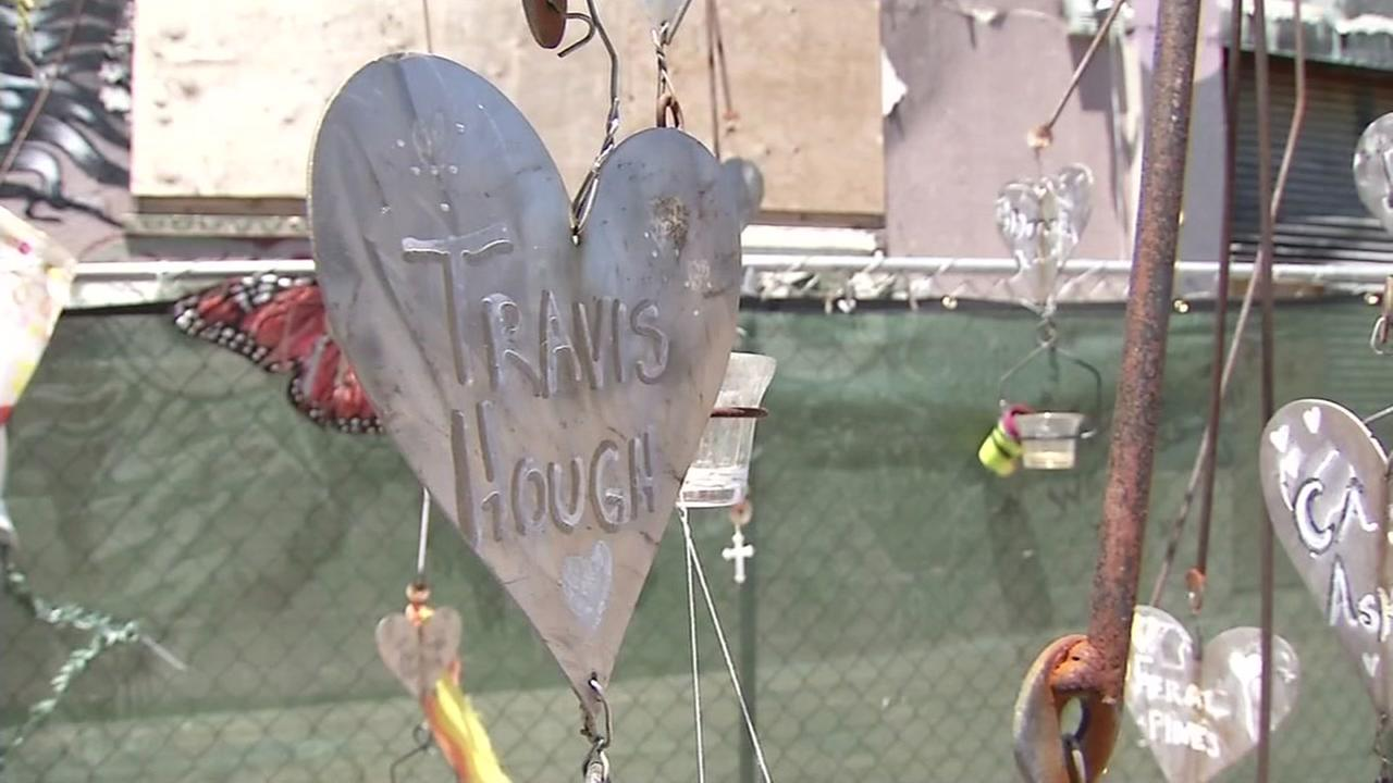 A heart with Travis Houghs name on it is seen in front of the Ghost Ship warehouse where 36 people lost their lives in a fire last December.