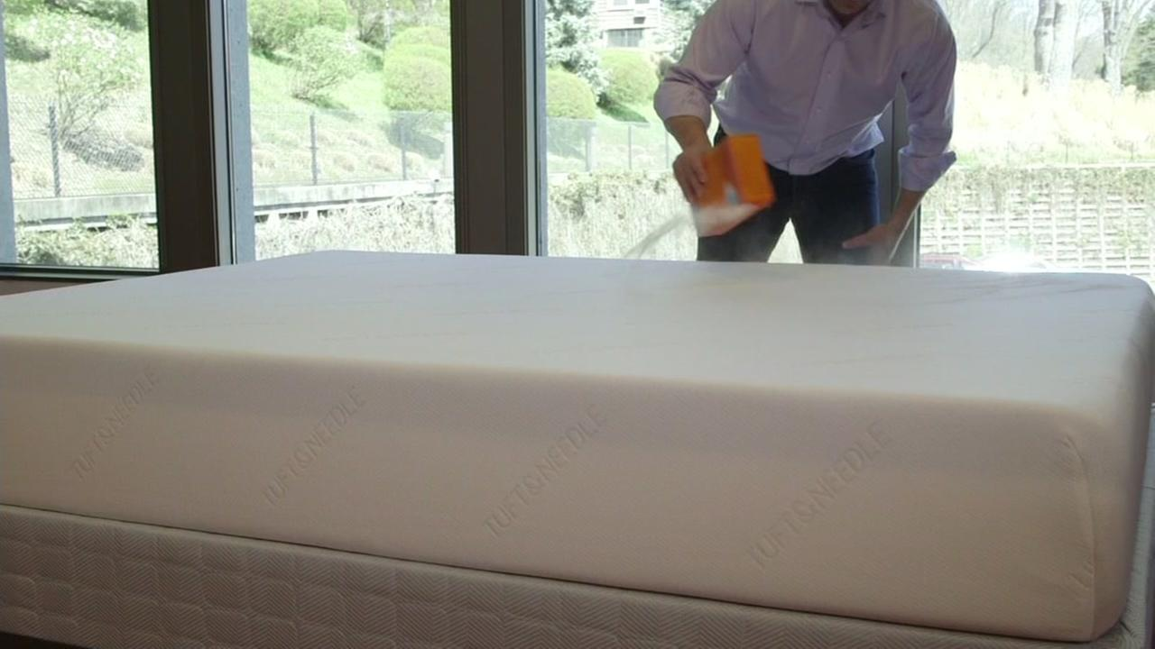 This is an undated image of a man cleaning a mattress with baking soda.