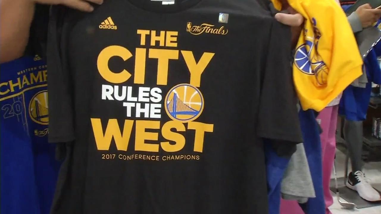 A fan holds up a Warriors championship t-shirt inside DICKs Sporting Goods store in San Jose, Calif. on Tuesday, June 13, 2017,