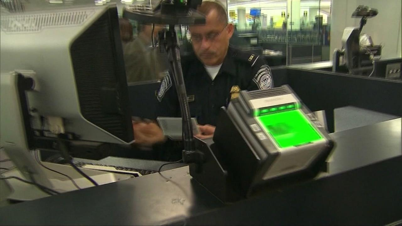 An employee is seen checking Visas and tickets at an airport in this undated image.