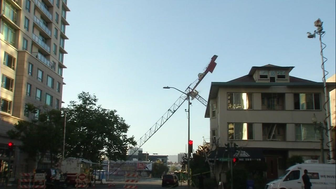 A crane is seen being toppled at the site of a massive fire in Oakland, Calif. on Saturday, July 8, 2017.