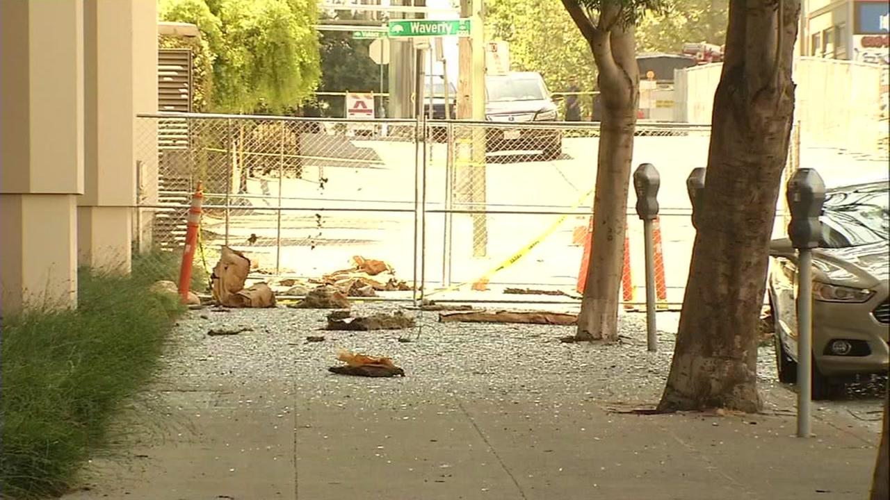 Broken glass is seen on the sidewalk on Sunday, July 9, 2017 across the street from an apartment building that burned down in Oakland, Calif. while it was under construction.
