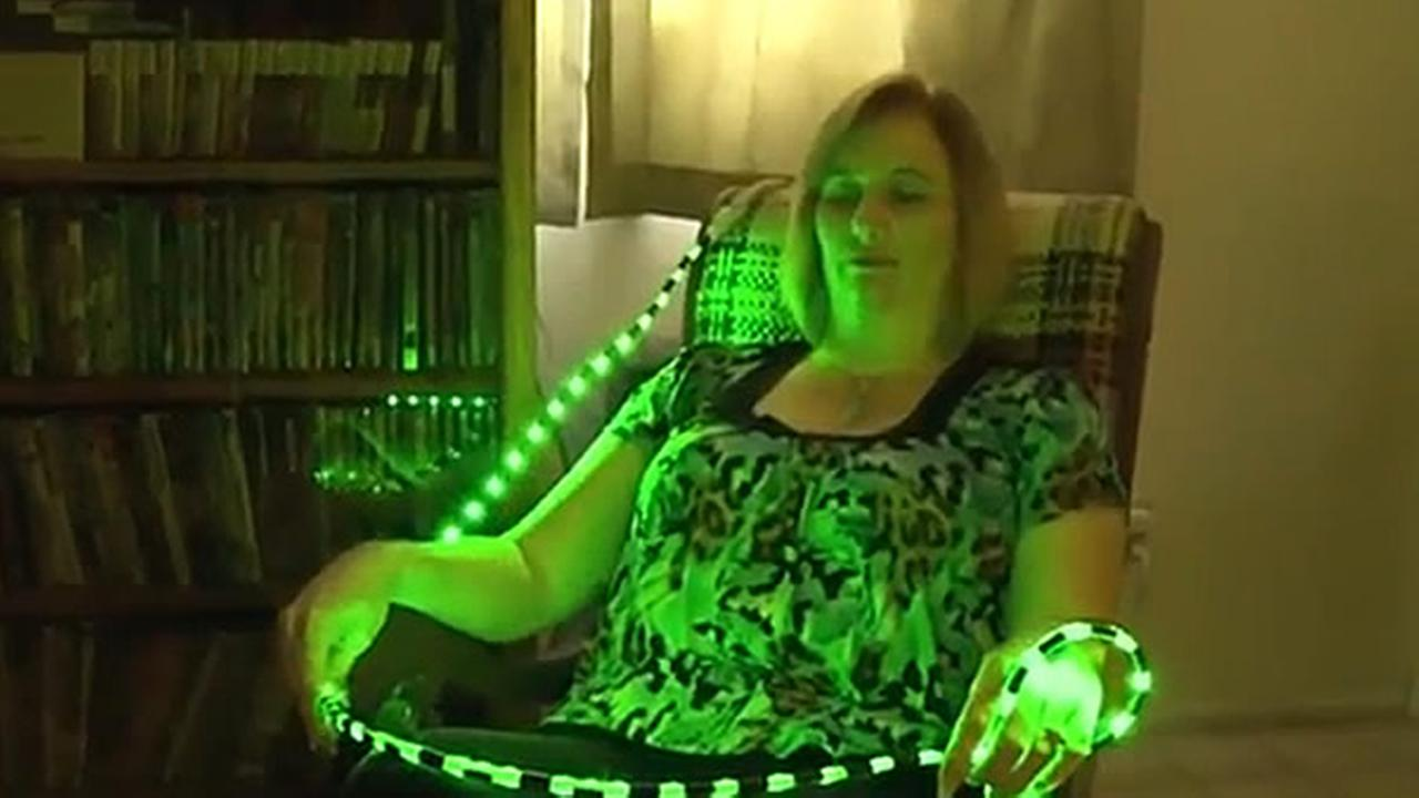 A woman is shown using green LED lights that help to treat her migraines.