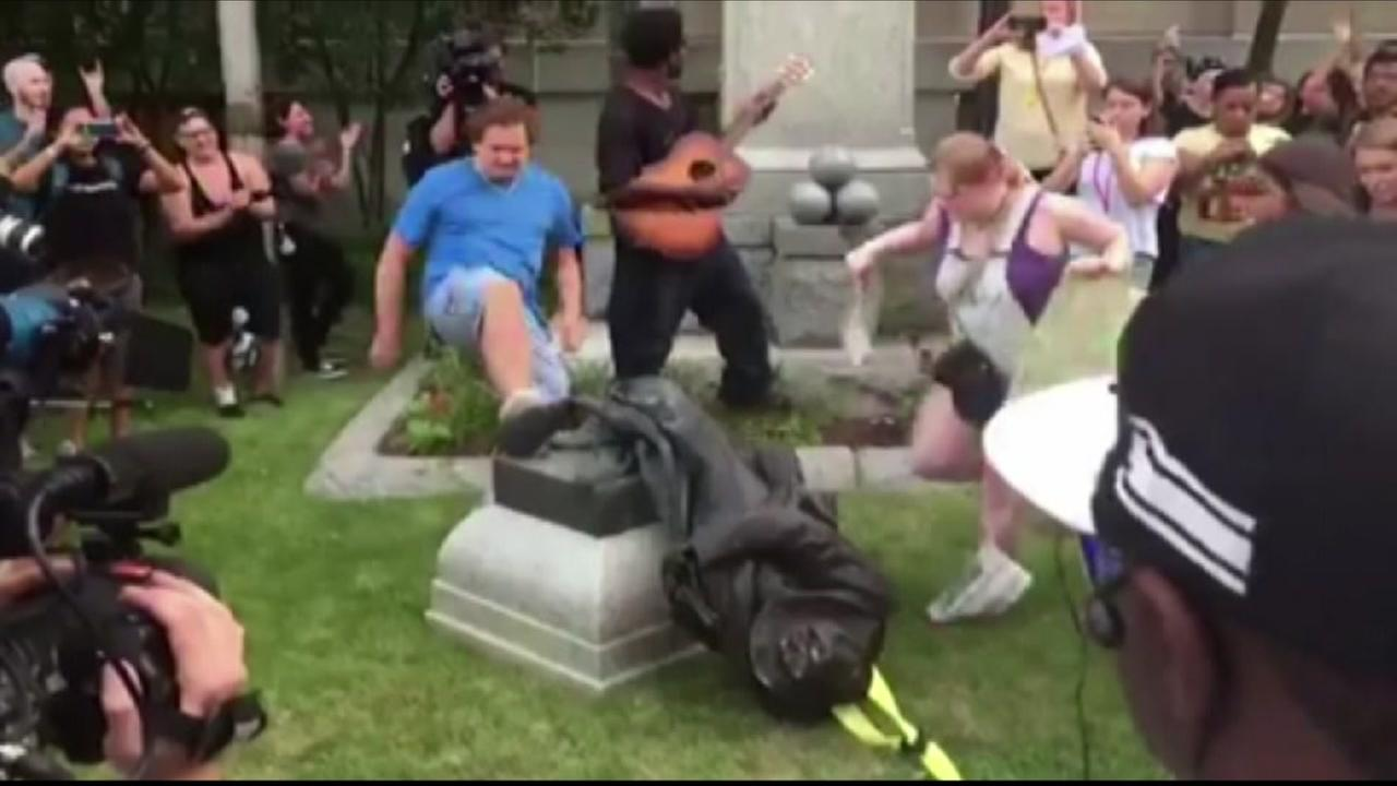 A man is seen kicking a Confederate statue in North Carolina, on Monday, August 14, 2017.
