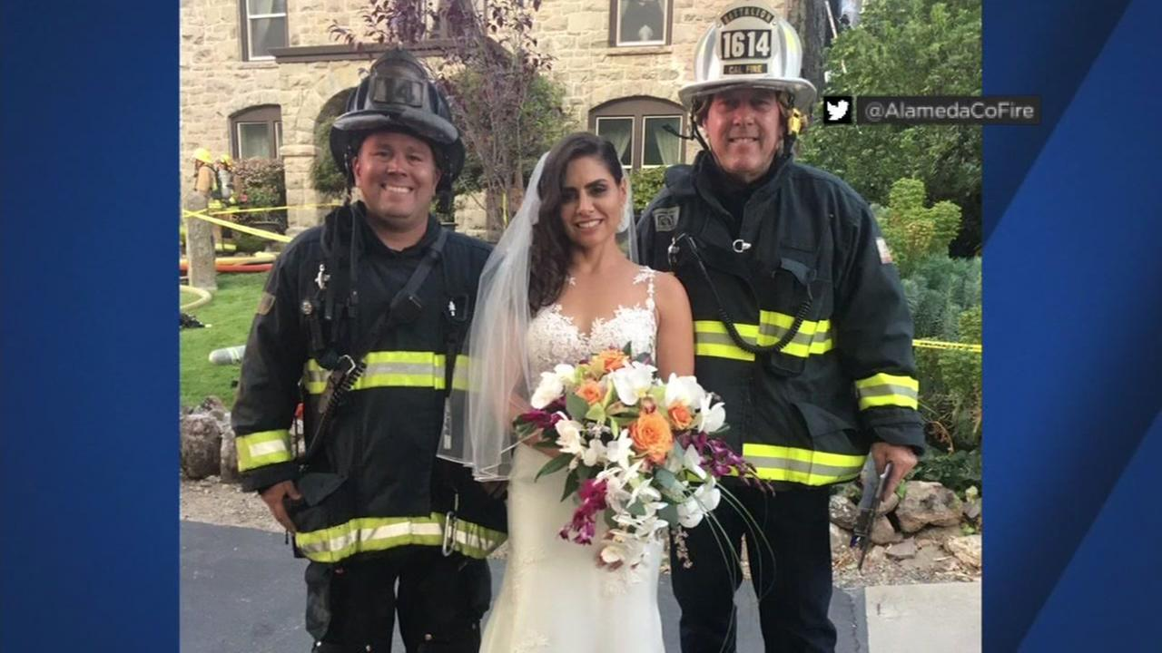 A bride is seen with Alameda County Firefighters after a fire at Elliston Winery in Sunol, Calif. interrupted her reception.