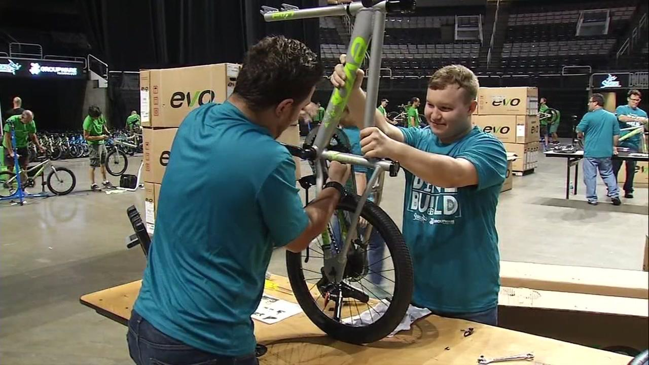 San Jose Sharks players and volunteers work to build bikes for local children at the SAP Center in San Jose, Calif. on Tuesday, August 22, 2017.