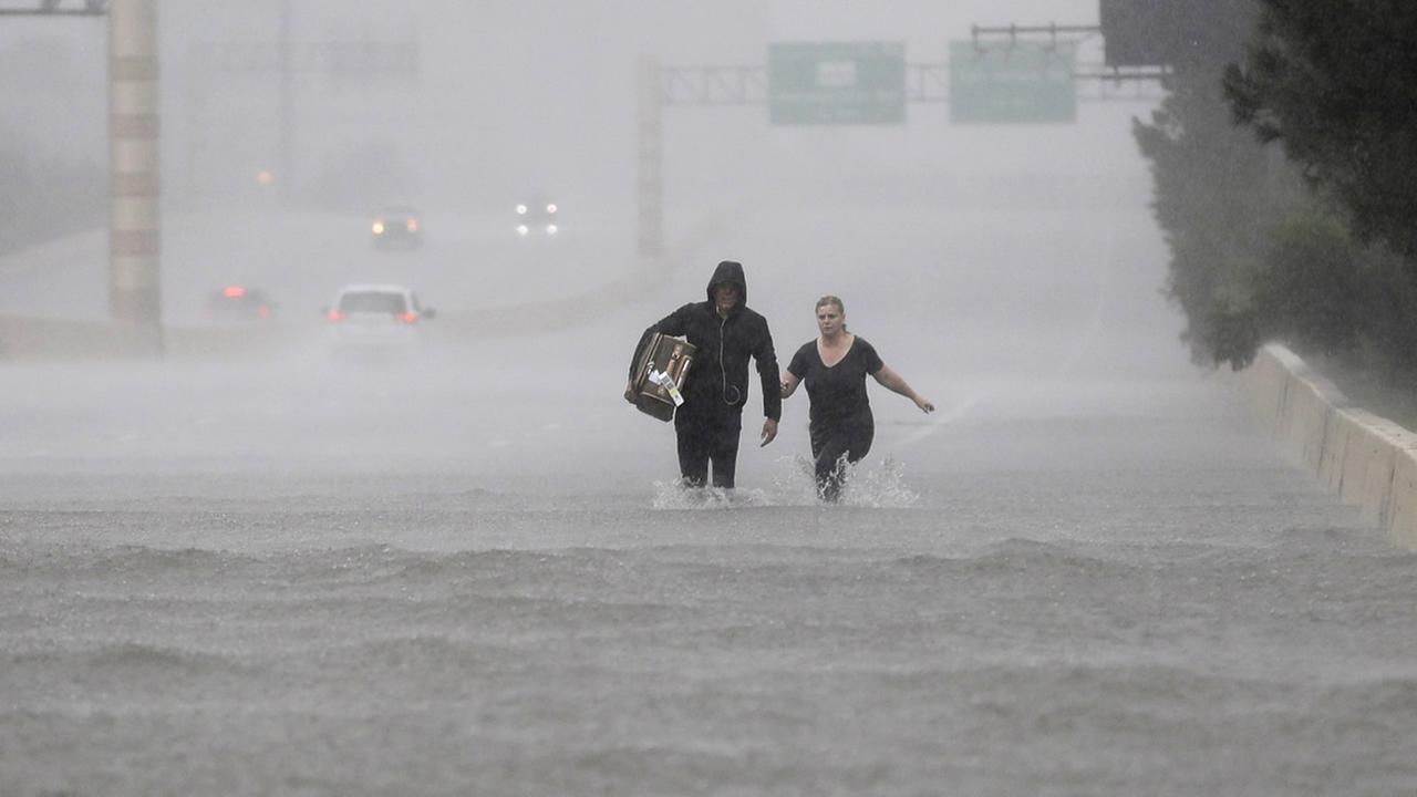Two people walk down a flooded section of Interstate 610 in floodwaters from Tropical Storm Harvey on Sunday, Aug. 27, 2017, in Houston, Texas. (AP Photo/David J. Phillip)