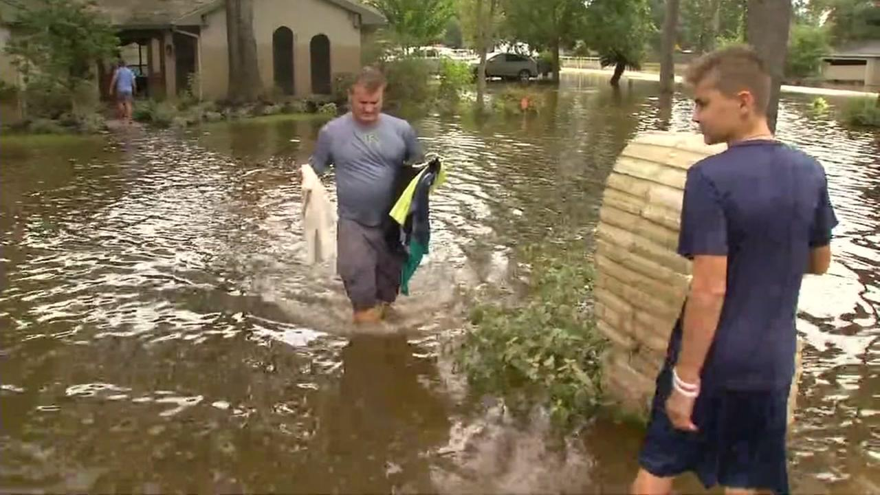 A father and son wade through flood waters near their home in Spring, Texas on Wednesday, Aug. 30, 2017.