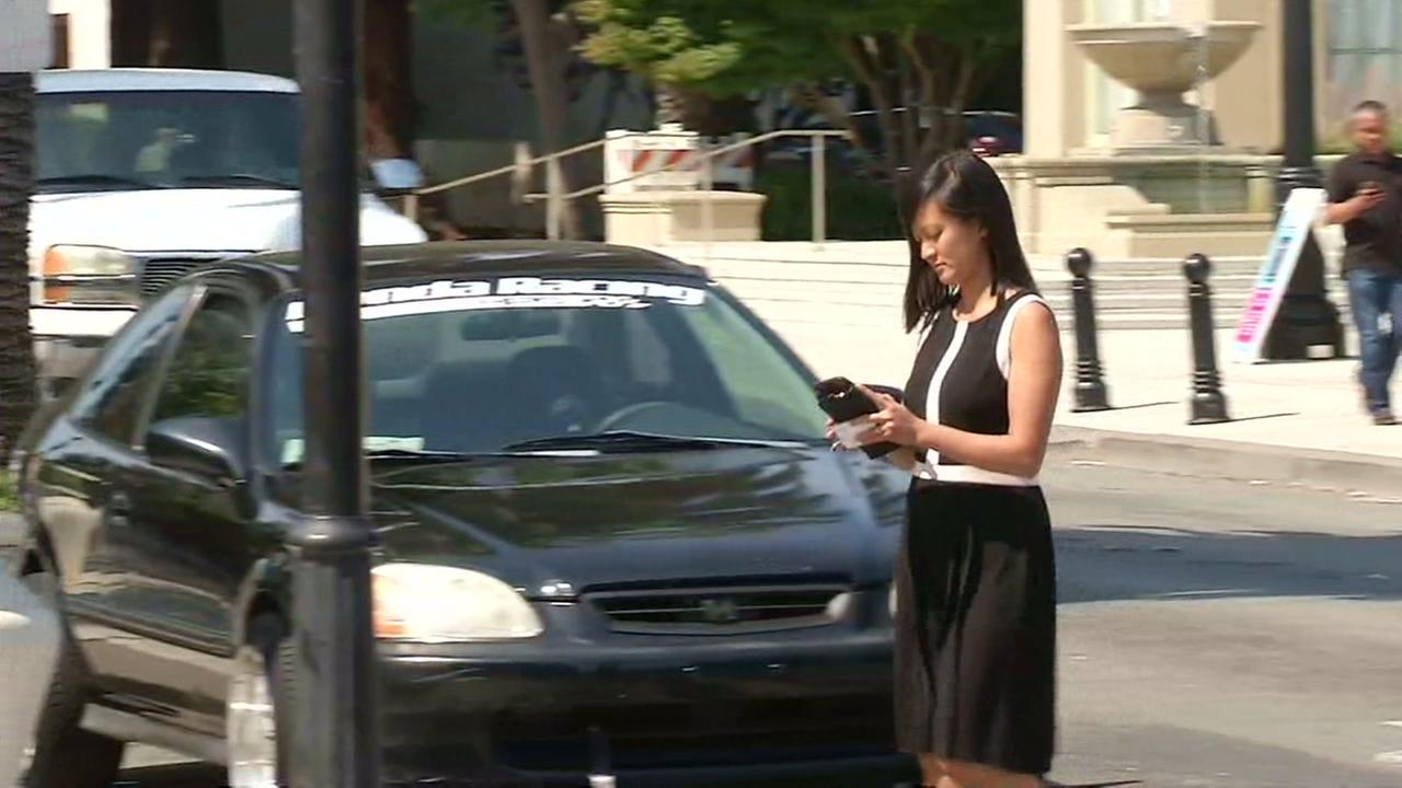 A woman is seen crossing a street while using a cellphone in this undated image.