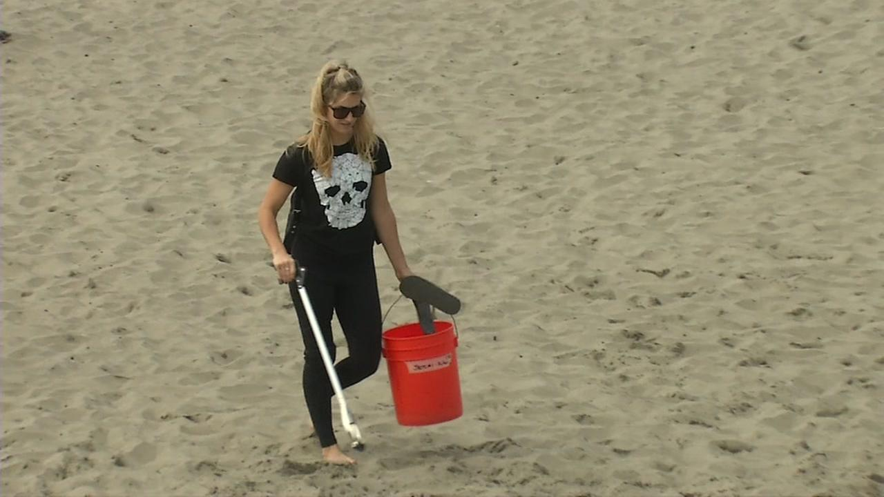 A volunteer is seen cleaning trash from a beach in San Francisco on Saturday, September 16, 2017.