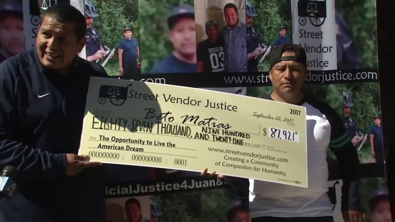 Hot dog vendor Beto Matias is seen holding a check for $87,000 from a GoFundMe campaign.