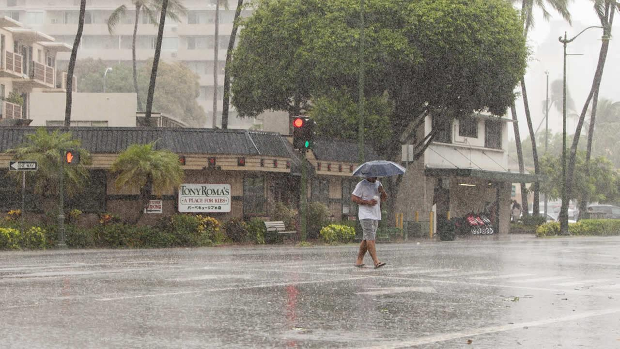 A man uses an umbrella against the rain as he walks across Kapiolani Blvd in Waikiki in Honolulu on Friday, Aug. 8, 2014. (AP Photo/Marco Garcia)